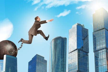 ballast: Businessman with iron ballast hopping over town