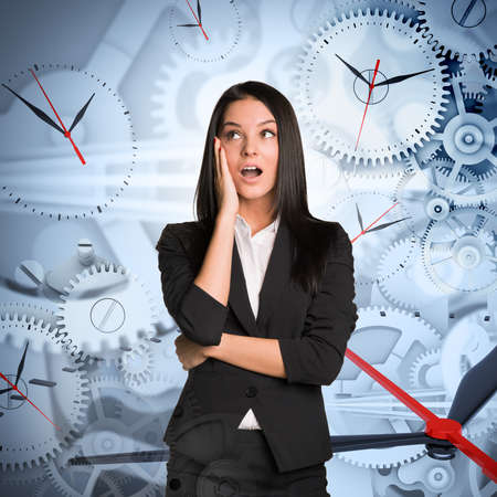 businesslady: Surprised businesslady on abstract background with clocks