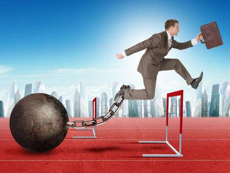 competitividad: Hombre de negocios con la maleta y el lastre de hierro saltando sobre barrera caminadora