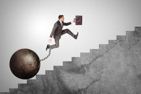 ballast: Image of confident businessman with suitcase and iron ballast running upstairs Stock Photo