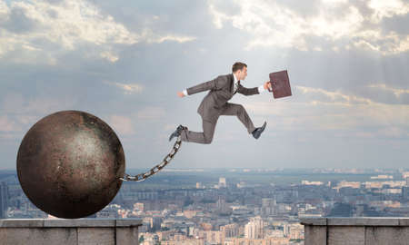 Image of young businessman with suitcase and iron ballast jumping over gap