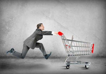 funny people: Businessman pushing shopping cart on grey wall background Stock Photo