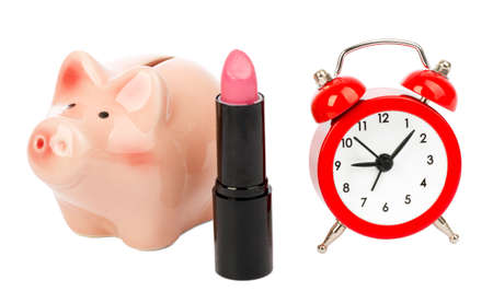 exaggerate: Lipstick with piggy bank and alarm clock on isolated white background Stock Photo