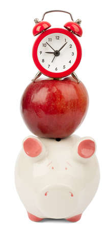ear: Fresh red apple with alarm clock and piggy bank on isolated white background