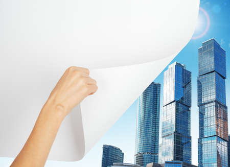 turning page: Hand turning page to city with skyscrapers Stock Photo