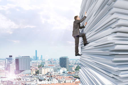 Businessman climbing up a huge stack of paper with city background Stock Photo