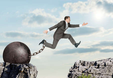 ballast: Image of young businessman with iron ballast jumping over gap