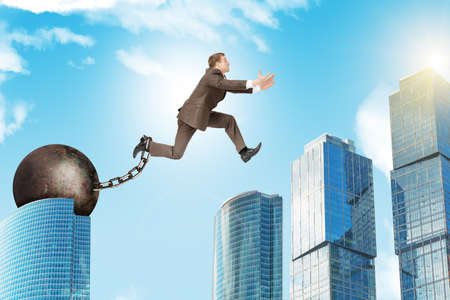ballast: Image of young businessman with iron ballast jumping over gap on city background