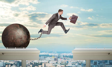 impediment: Image of young businessman with suitcase and iron ballast jumping over gap