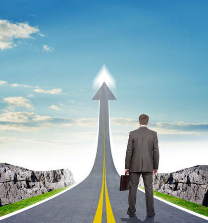 Businessman standing on highway road going up as an arrow in sky