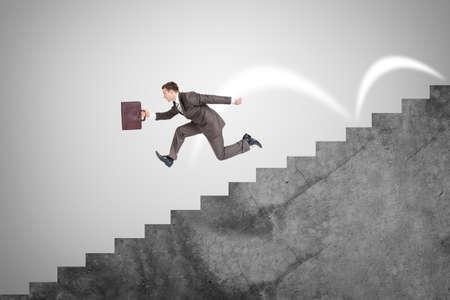 down stairs: El hombre de negocios con la maleta que se ejecuta rápidamente por las escaleras