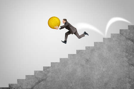 down the stairs: Hombre de negocios con gran moneda de oro que se ejecuta rápidamente por las escaleras