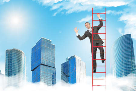 climbing ladder: Happy businessman climbing ladder on blue sky background Stock Photo