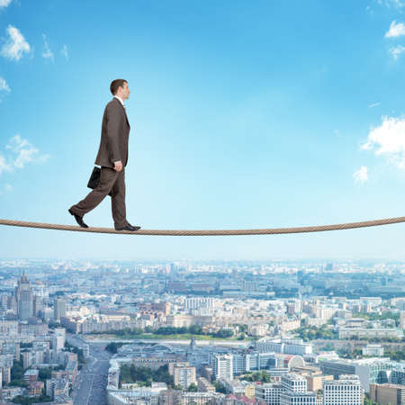 councilor: Businessman walking on rope on blue sky background
