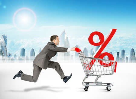 shopping cart: Running businessman with percent sign in shopping cart