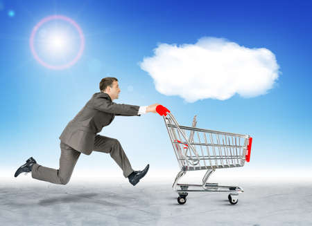 empty shopping cart: Running businessman with empty shopping cart and cloud