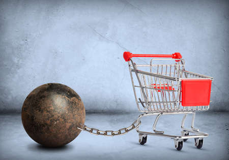Iron ball with chain and empty shopping cart, closeup Stock Photo