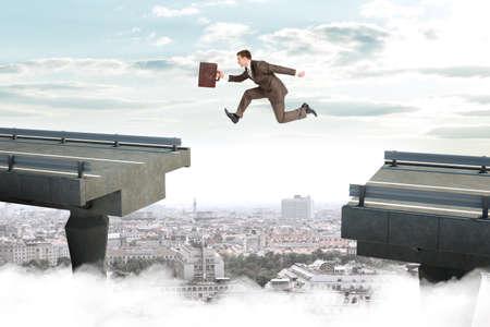 Beeld van jonge zakenman met koffer die over hiaat van gebroken brug springt Stockfoto
