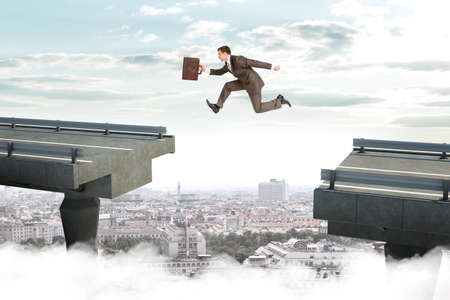 bridge the gap: Image of young businessman with suitcase jumping over gap of broken bridge Stock Photo