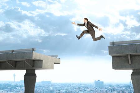 Afbeelding van jonge zakenman springen over de kloof van de gebroken brug