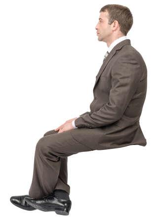 gente sentada: El hombre de negocios sentado en el lugar vacío en el fondo blanco, vista lateral Foto de archivo