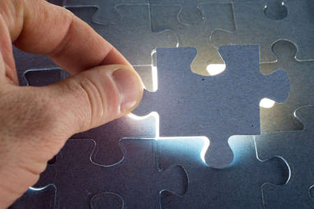 final piece of puzzle: Missing jigsaw puzzle piece with light glow, for completing the final puzzle piece Stock Photo