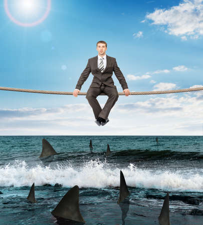 councilor: Businessman sitting on rope above ocean with sharks and looking at camera Stock Photo