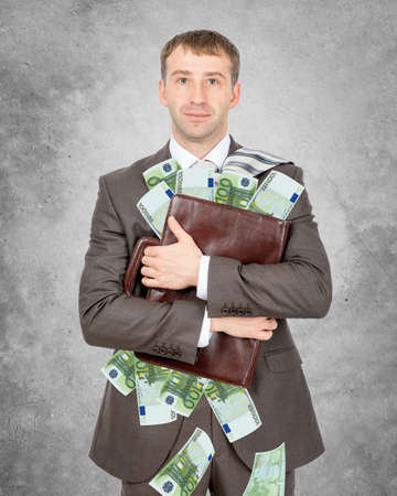 Businessman holding suitcase with oiles of euro looking at camera