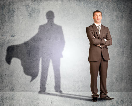 shadow: Businessman with superman shadow looking at camera Stock Photo