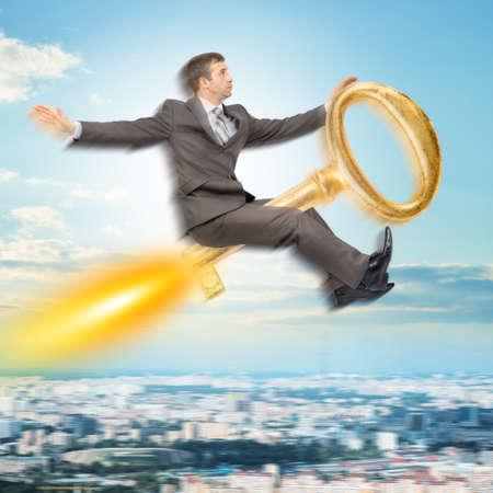 gold key: Businessman flying on gold key above city