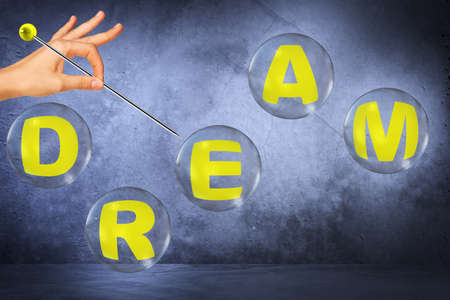 blow out: Word dream in bubbles and female hand with needle try to blow out bubbles on grey background Stock Photo