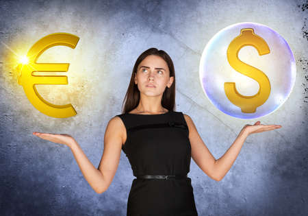 busineswoman: Busineswoman holding dollar sign in big bubble and euro sign on grey background Stock Photo