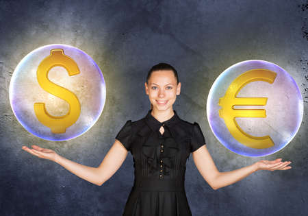 busineswoman: Woman holding dollar and euro signs in bubbles on grey background Stock Photo