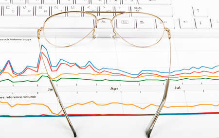 graphical: Keyboard with eyeglasses and graphical charts, closeup Stock Photo