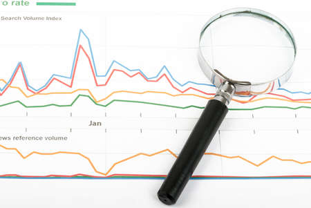 graphical: Magnifier with graphical charts background, close up view