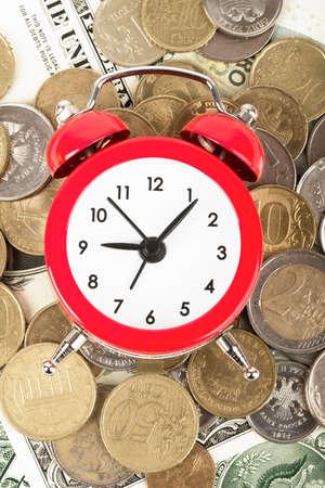 minute hand: Red alarm clock on cash backgound, closeup