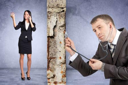 businesslady: Businessman with stethoscope hearing grey wall with businesslady Stock Photo