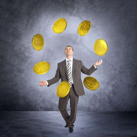 juggle: Businessman juggling big coins on abstract grey background Stock Photo