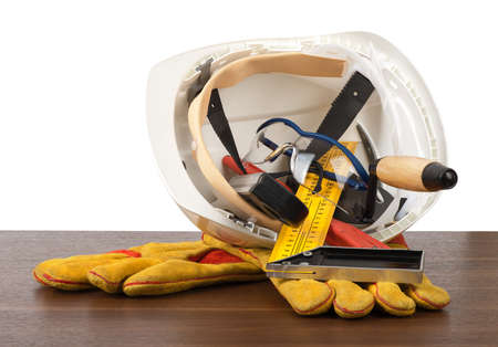 protective work wear: Plastic safety helmet with protective gloves and tools on table isolated on white background