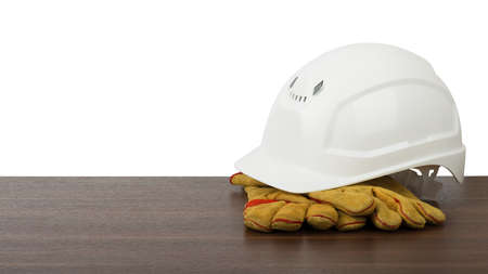 protective work wear: Plastic safety helmet with protective gloves on table isolated on white background
