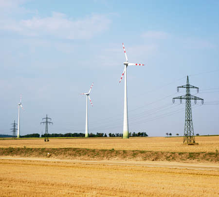 windfarms: Set of wind farms on field with blue sky background