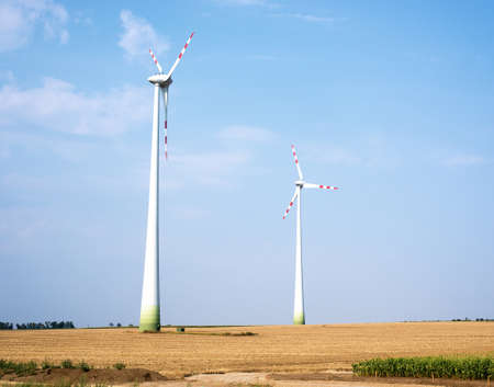 windfarms: Two wind farms on field with blue sky background