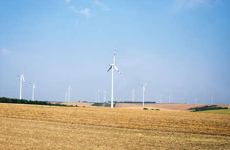 windfarm: Set of wind farms on field with blue sky background