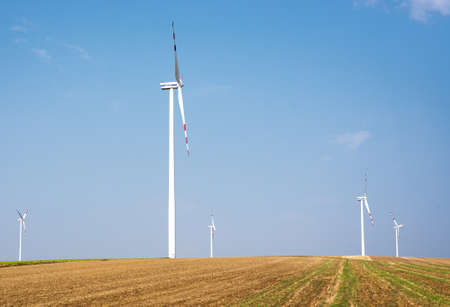 windfarm: Wind farms on field with blue sky background Stock Photo