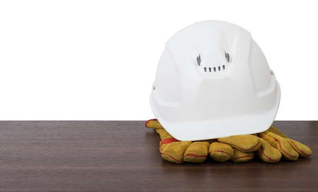 protective work wear: Plastic safety helmet with protective gloves on table isolated on white background, front view Stock Photo