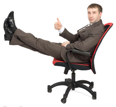 legs up: Businessman sitting on chair with legs up and showing ok isolated on white background, side view