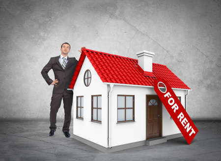 Businessman with house for rent on grey wall background
