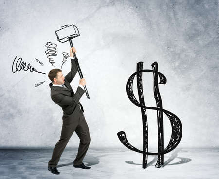 dollar signs: Businessman with hammer and dollar sign on grey wall background