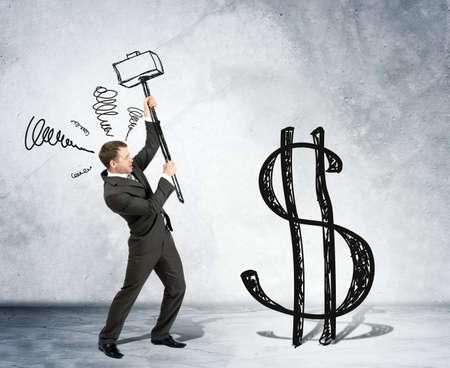 signos de pesos: El hombre de negocios con el martillo y el signo de dólar en el fondo de la pared gris