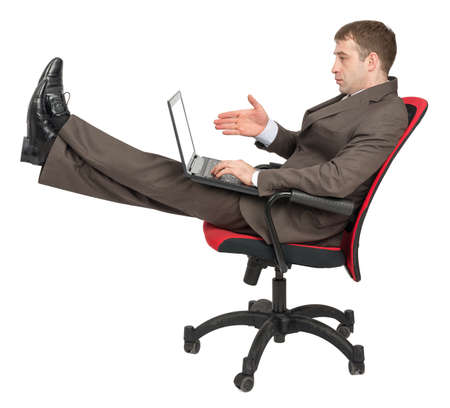 legs up: Businessman sitting on chair with laptop and legs up isolated on white background, side view Stock Photo